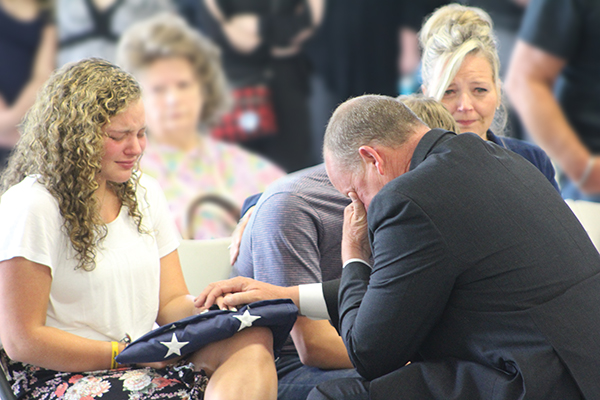 Press photo/Jake Browning - Jeslyn Head, daughter of David Head, is presented with an American flag and Head's service badge by sheriff Robert Holland during the service.