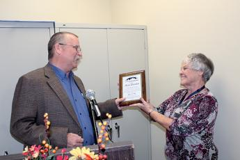 Press photos/Jake Browning - Kathy Kahler presents Alan Durden with a plaque marking his 30 years as cooperative extension director.
