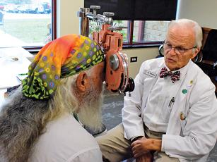 Press photo/Linda Mathias - Dr. LeRoy Roberson performs an eye exam for a veteran during Thursday's Stand Down.