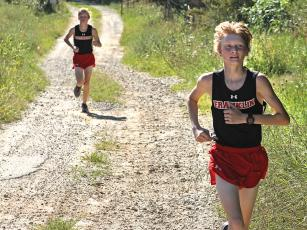 Press photo/Andy Scheidler - Ethan Stamey leads his brother Nathan by a few strides during a meet in August at Rabun Gap-Nacoochee School. The twins finished 11th and 16th at the 2-A NCHSAA Championship this past weekend in Kernersville. Franklin's boys finished ninth, while girls placed 15th.