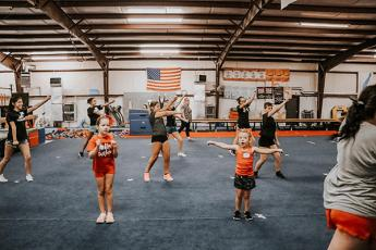 Photo/Alyssa Burk - Ruby Red cheerleaders practice a routine inside New Vision Training Center in Franklin.
