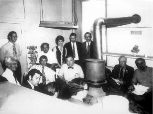 County commissioners and other local officials meet around a pot-bellied stove in the old courthouse in this photo from about 1970. That's Dick Jones standing by the stovepipe, next to Sheriff George Moses. Press editor Bob Sloan is standing to the right of a poster for an Ox Roast Festival. County manager Ron Winecoff is in front of Sloan and County Chairman Oscar Ledford is sitting beside him. Also shown are the two other county commissioners and members of the Highlands town board.