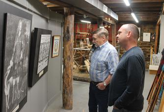 Press photo/Will Woolever - Scottish Tartan Museum director Jim Akins and new Blair Building owner Stacy Guffey examine a piece of artwork in the museum's basement.