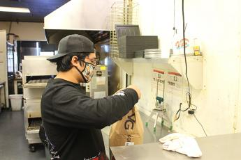 Press photo/Will Woolever - Papa's Pizza To Go owner Eric Olvera opens a bag of flour while preparing for the day's service. Olvera does not know whether Papa's will be allowed to stay in its current location during renovations.