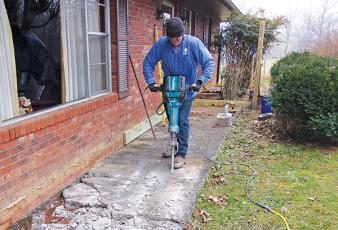 Submitted photo/Habitat - John Wert of Habitat for Humanity removes a sidewalk at Vaughn Sanders' home as part of the Healthy Home Initiative. The sidewalk was sunken and too narrow for Sanders' wheelchair, so the construction crew replaced it with a front porch and ramp.