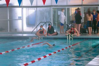 Press Photo/Will Woolever FHS swimmers Natalie Ballard (left) and Olivia Stahl help teammates keep track of how many laps they've swum  in the 500-meter freestyle against Smoky Mountain. The event requires swimmers to go ten laps, or twenty lengths of the pool.
