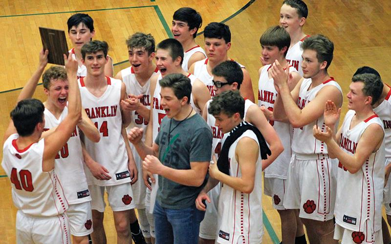 Bradley Stiles (40) holds up the plaque while his teammates react after winning the Mountain Six Conference tournament for junior varsity boys basketball. Franklin went 23-1 this season and dominated Smoky Mountain in the finale.