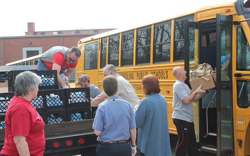 Press photo/Jake Browning - Volunteers at Franklin High School load breakfasts and lunches onto a bus to deliver to local students.