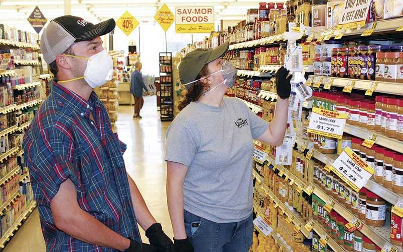 Press photo/Jake Browning - Max Falcon and Megan Nicholson wear masks to protect themselves on a shopping trip to Sav-Mor.