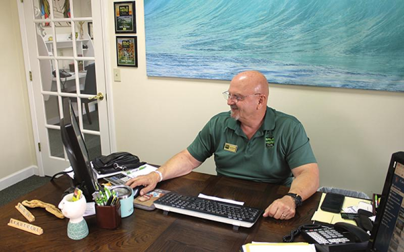 press photo/Will Woolever - Bald Head Realty owner/broker John Becker checks the company website in his Franklin office.