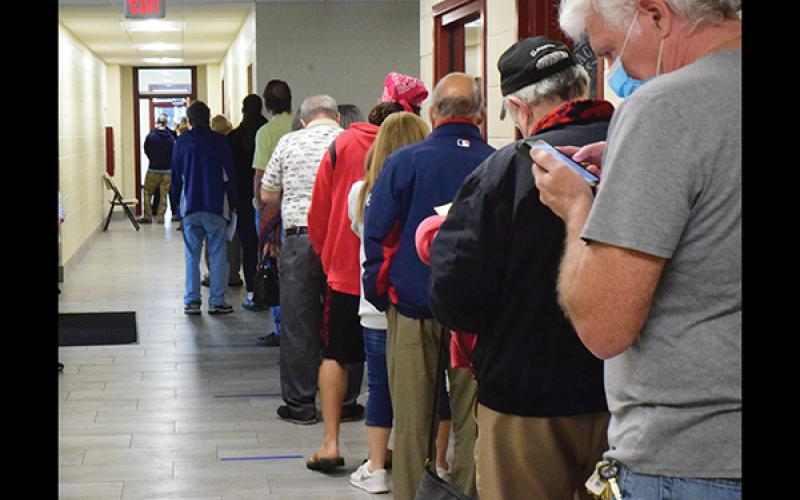 Press photo/Linda Mathias Voters line up at the Robert C. Carpenter Community Building to cast ballots in early voting.