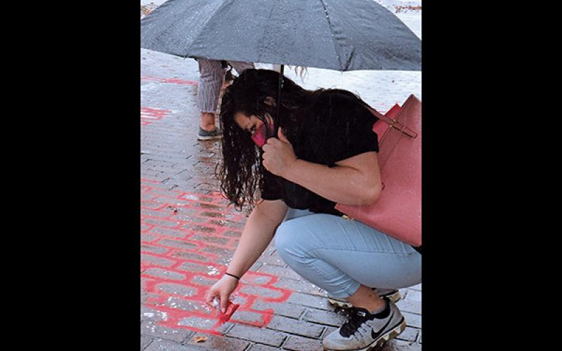 Press photo/Linda Mathias - Kuteka Lopez pours red sand outside the Macon County Courthouse to draw attention to victims of human trafficking.