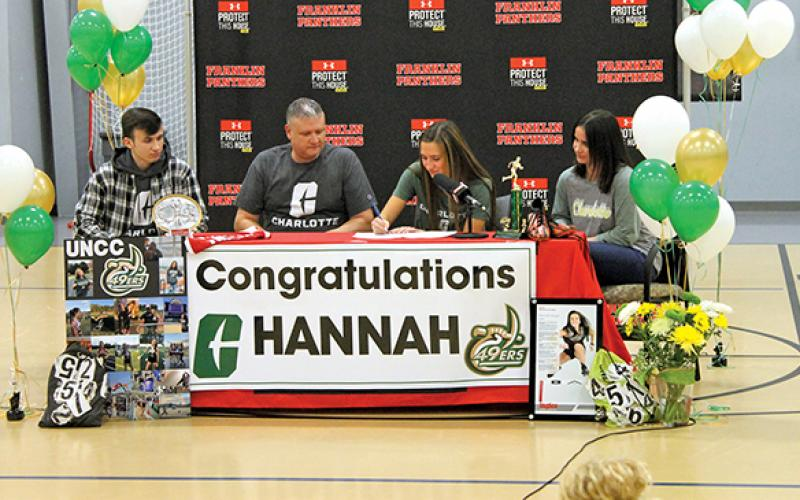 Press Photo/Will Woolever - Senior track and field star Hannah Angel (center right) signs her official offer letter from UNC Charlotte while her brother, Phillip (left); dad, Jeremy; and mom, Jennifer, look on.