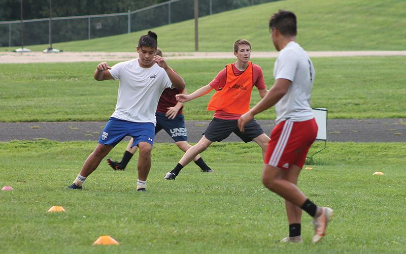 Press photo/Will Woolever - FHS soccer players (from left) Pablo Montelongo, Luke VanHook and Bryan Rodriguez take part in a preseason conditioning drill. The team has been holding unofficial workouts since June.